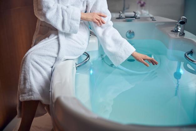 Primo piano su una donna seduta sul bordo della vasca con la retroilluminazione blu