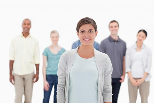 Primo piano di una donna che sorride con le persone dietro di lei
