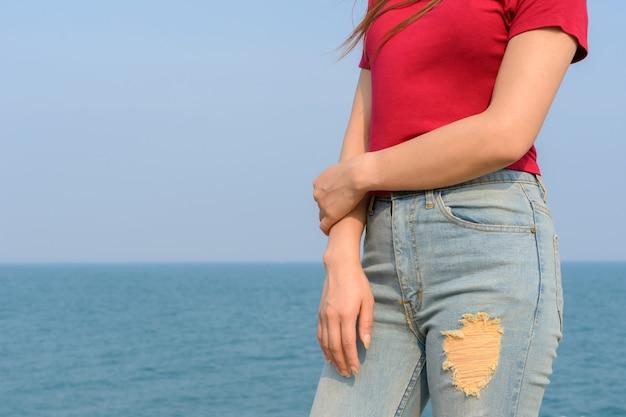 Close up donna in piedi indossando t-shirt rossa e jeans con mare e cielo blu dietro