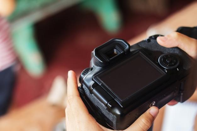 Primo piano di donna prendere foto dalla fotocamera dslr.