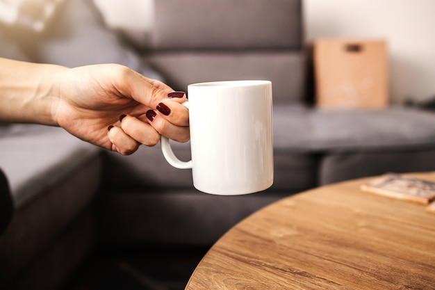 Chiuda in su della donna che cattura arabica caffè fresco del mattino da un tavolo.
