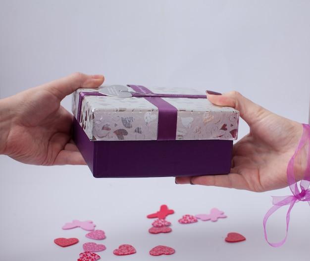 Primo piano della donna che prende presente dal suo fidanzato. san valentino. amore e regali.