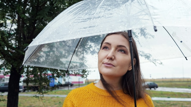 Primo piano di una donna sotto un ombrello trasparente in caso di pioggia