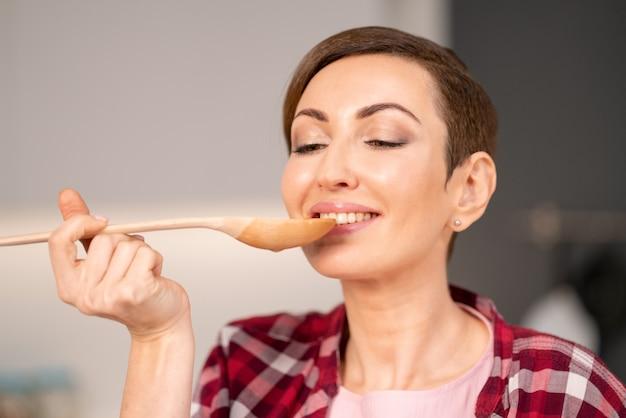 Primo piano di una donna che prova un piatto cucinato usando un cucchiaio di legno lungo.