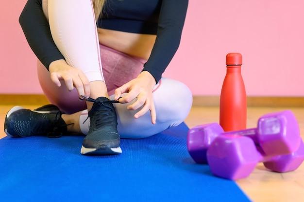Primo piano di donna che lega i lacci delle scarpe da ginnastica prima dell'esercizio.