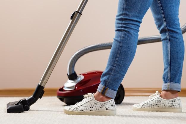 Primo piano di una donna aspirapolvere il tappeto