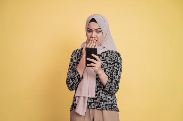 Primo piano di una donna in velo che usa un telefono cellulare scioccata quando vede lo schermo di un telefono cellulare con co...