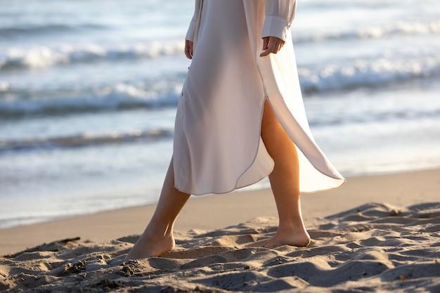 Chiuda sulla donna che cammina sulla spiaggia