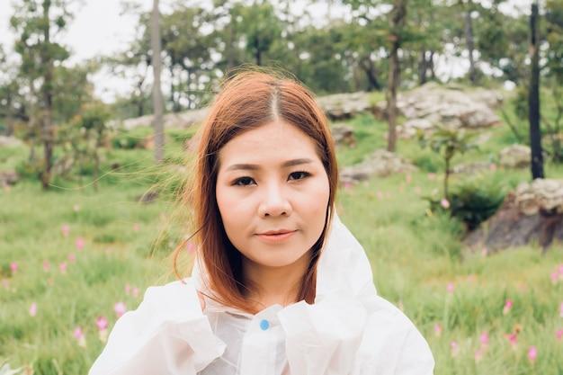 Close up donna indossare impermeabile stand nella foresta pluviale