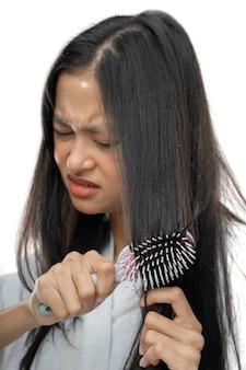 Primo piano di una donna che indossa un asciugamano è infastidita dal fatto che i suoi capelli siano aggrovigliati quando vengono pettinati