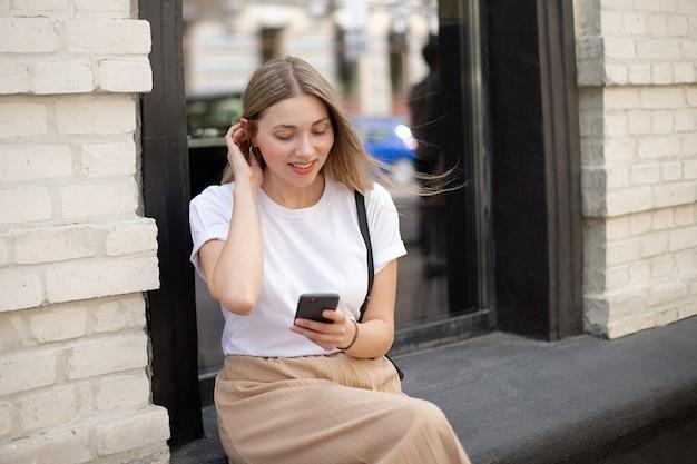 Primo piano di una donna con una maglietta bianca guarda il telefono e si raddrizza i capelli mentre è seduta per strada sullo sfondo di una grande finestra vicino a un edificio in mattoni