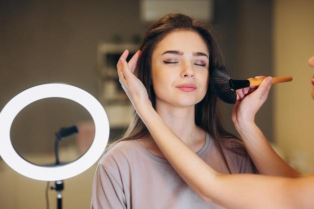 Primo piano di una donna con i capelli castani che si trucca. pennello da trucco vicino al viso.