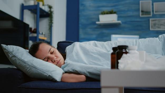 Primo piano di una donna con una malattia che dorme in una coperta sul divano