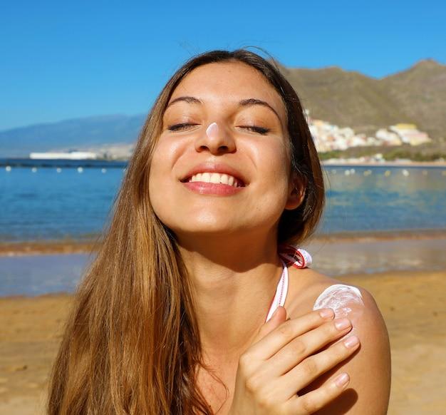 Primo piano di donna con gli occhi chiusi applicando crema solare