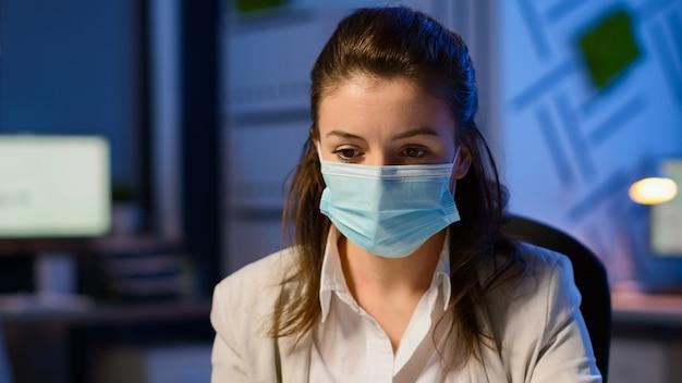 Primo piano di una donna con maschera facciale che legge e-mail a tarda notte per rispettare la scadenza del progetto lavorando nel nuovo normale ufficio aziendale, prendendo appunti, analizzando i documenti durante la pandemia globale