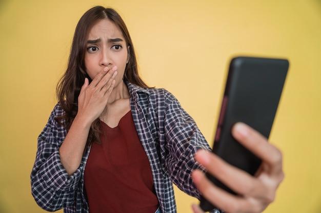 Primo piano di una donna con i capelli lunghi che usa un telefono cellulare scioccata quando vede lo schermo di un telefono cellulare ...