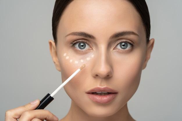 Chiuda in su della donna con trucco naturale che applica il correttore sulla pelle fresca impeccabile, facendo il trucco.