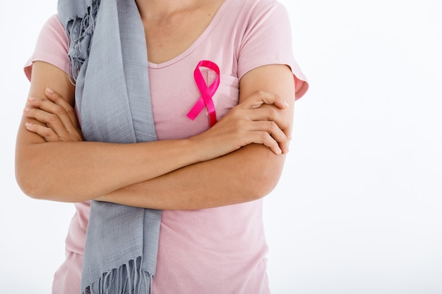 Primo piano di donna con nastro rosa per la consapevolezza del cancro al seno isolato su sfondo rosa per studio spazio copia vuoto, assistenza sanitaria, concetto di medicina