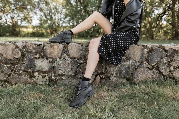 Donna del primo piano con gambe sexy in giacca di pelle nera alla moda in abito elegante con stivali alla moda su pietre sulla natura in primavera. vestiti primaverili di moda giovanile per le donne. sguardo quotidiano. particolari.