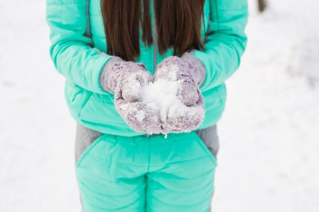 Primo piano di una donna con la neve sullo sfondo di natale