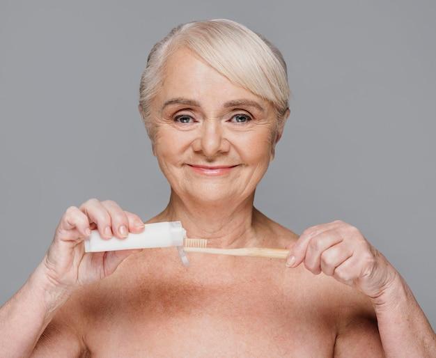 Donna del primo piano con spazzolino da denti e dentifricio