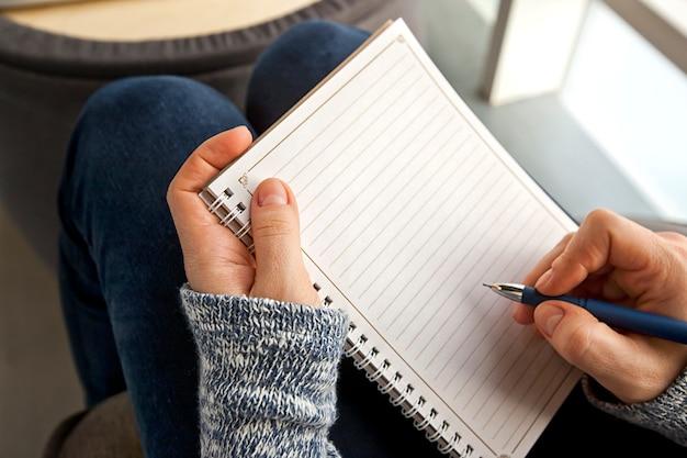 Primo piano sulla donna che scrive nel blocco note