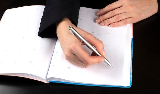Primo piano di una pianificazione di scrittura della donna nel diario del calendario sulla scrivania nera