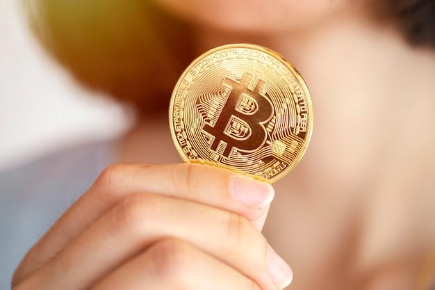 Primo piano della mano di una donna che tiene una moneta in criptovaluta