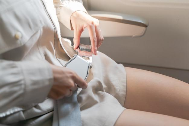 Close up delle donne allacciare la cintura di sicurezza sull'aereo.