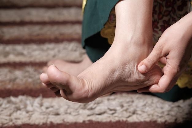 Primo piano sui piedi delle donne e massaggio alle mani sul punto della lesione