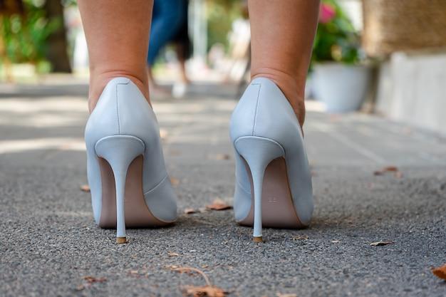 Chiuda in su dei piedi delle donne in piedi su scarpe blu col tacco alto