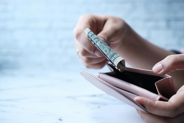 Chiuda in su della mano delle donne che risparmia contanti nel portafoglio