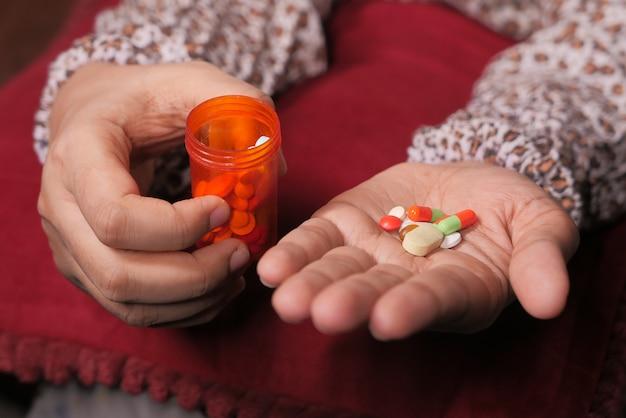 Chiuda in su della mano delle donne che prendono le pillole.