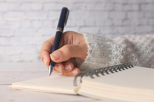 Close up delle donne la scrittura a mano sul blocco note.