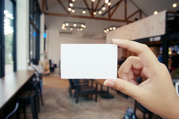 Chiuda su delle mani delle donne che tengono lo schermo dello spazio della copia in bianco della carta di ragione sociale.