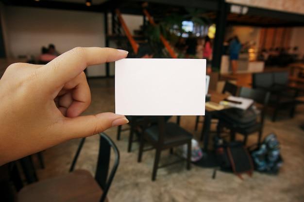 Primo piano di donne le mani che detengono il nome della carta di affari in bianco spazio di copia dello schermo