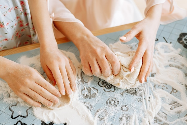 Primo piano delle mani di donne e bambini sullo sfondo del tavolo della cucina stanno preparando la pasta.