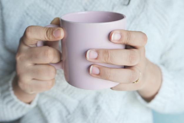 Primo piano della mano delle donne che tiene la tazza di caffè di colore rosa.