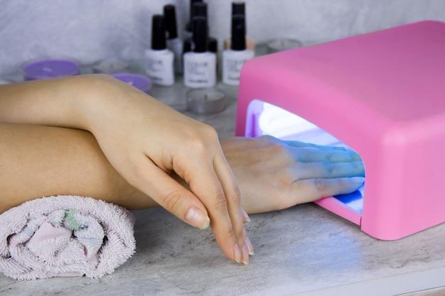 Chiuda in su della lampada di secchezza della mano e dello smalto delle donne, processo del manicure nel salone di bellezza