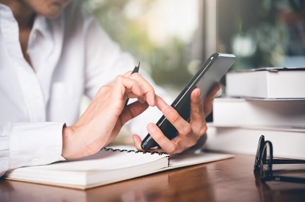 Chiuda in su della mano delle donne utilizzando il cellulare o il cellulare per il sito web di ricerca, dati, social network con comunicazione.