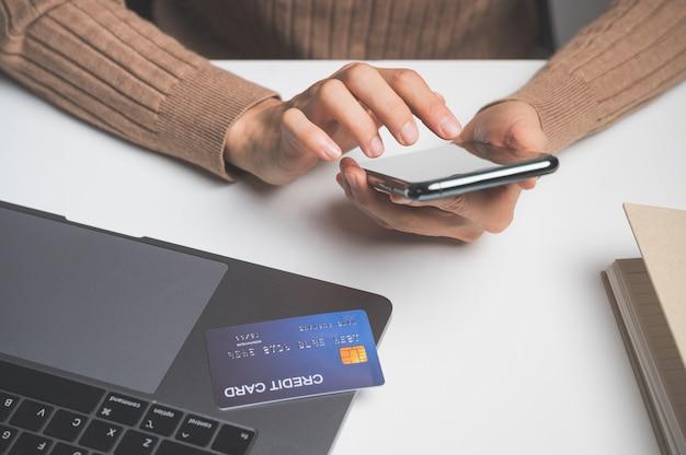 Chiuda in su della mano delle donne tramite cellulare o mobile per lo shopping online o il pagamento con carta di credito.