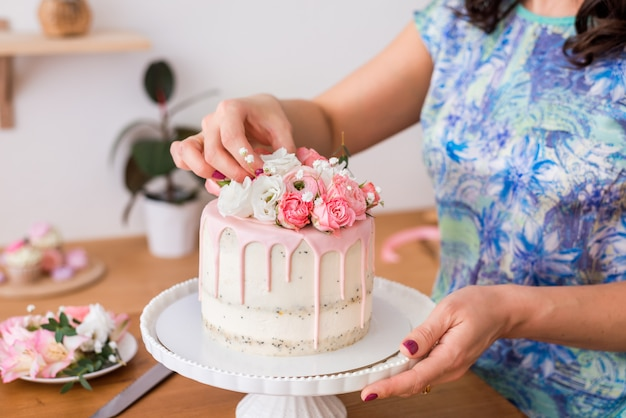 Primo piano delle mani delle donne che decorano la torta con fiori freschi.