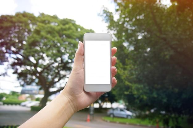 Primo piano delle mani delle donne in possesso di cellula telefono vuoto spazio copia dello schermo. telefono astuto con concetto di tecnologia.