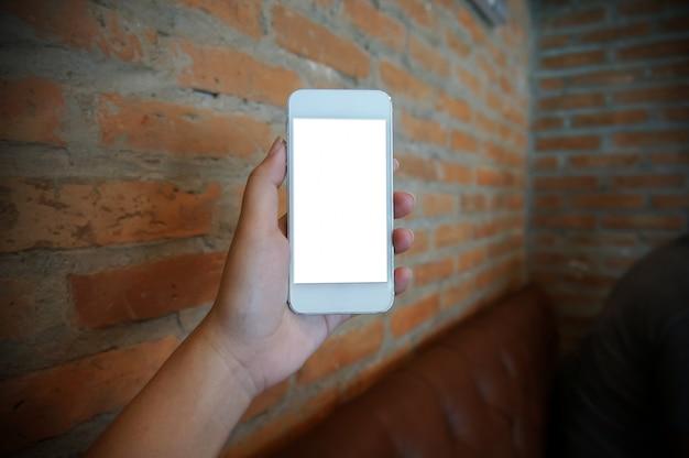 Primo piano delle mani delle donne in possesso di cellula telefono vuoto spazio copia dello schermo. telefono astuto con concetto di tecnologia