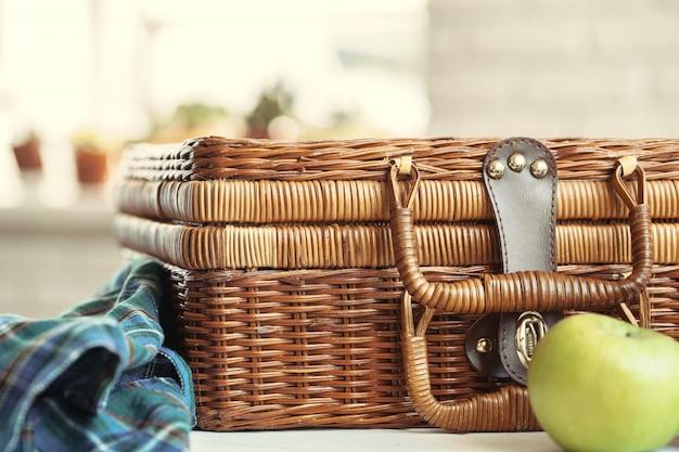Chiuda in su di un cestino di legno con le stoviglie sulla tabella bianca