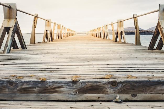 Primo piano del molo di legno sulla spiaggia in una giornata di sole in un luogo roccioso - lanzarote, isole canarie