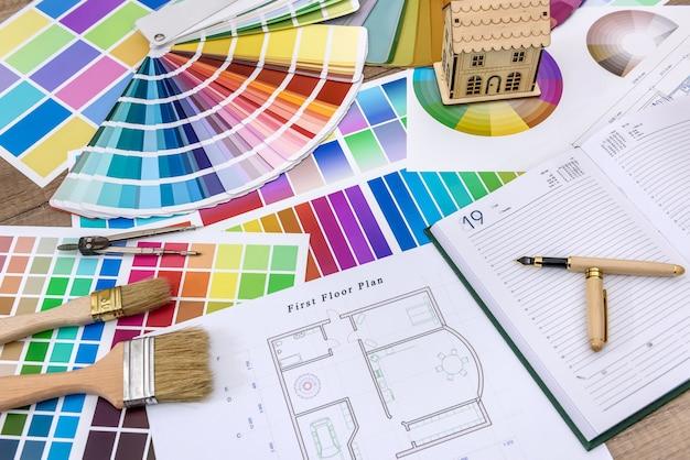 Primo piano del modello di casa in legno con blueprint e campioni di colore