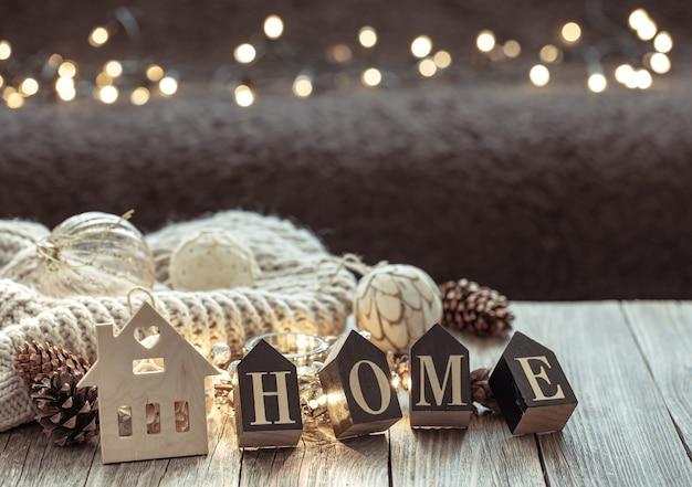 Primo piano di lettere in legno rendono la parola casa, su sfondo sfocato con bokeh.