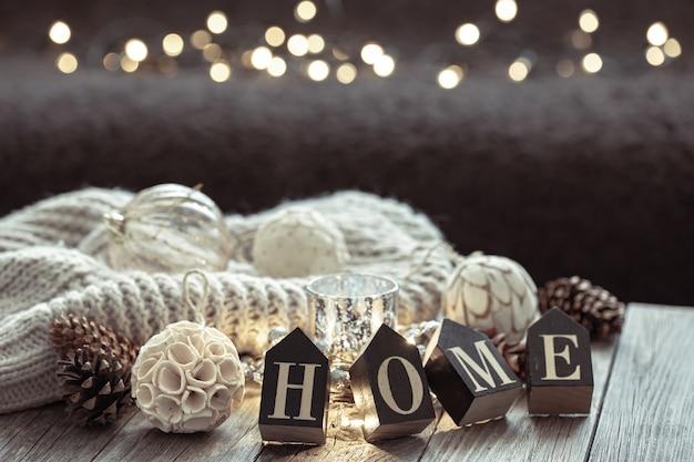 Primo piano di lettere in legno rendono la parola casa, dettagli di decorazioni natalizie su sfondo sfocato con bokeh.