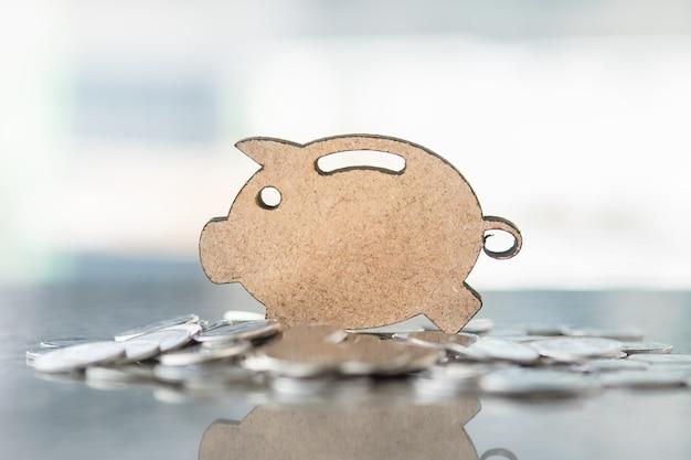 Close up di legno salvadanaio simbolo sulla pila di monete